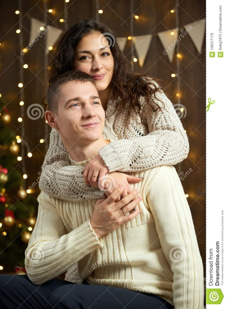 couple in christmas lights and decoration dressed in white young