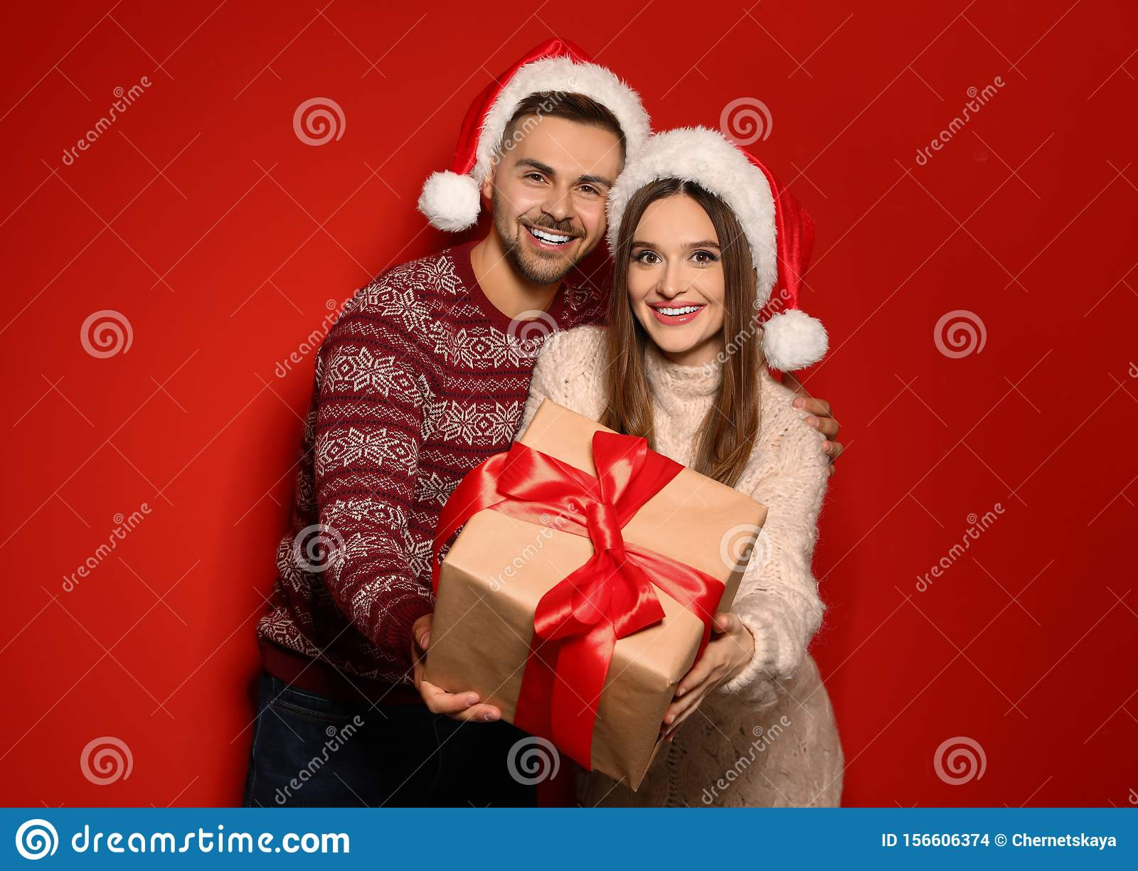 Couple in Christmas sweaters and Santa hats with gift box