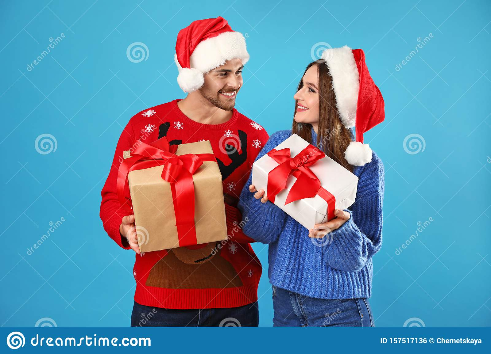Couple in Christmas sweaters with Santa hats and gift boxes