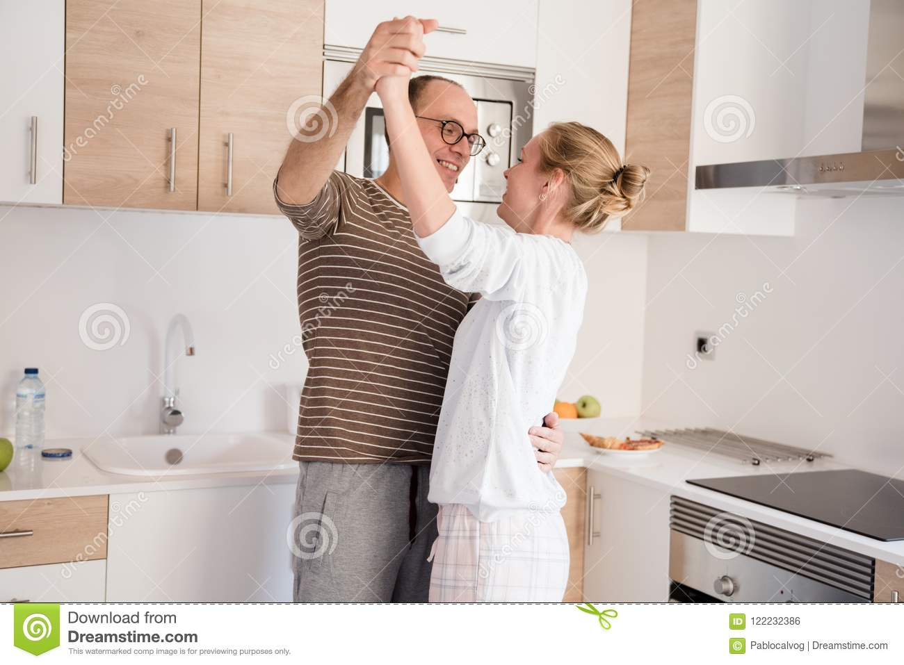 Couple holding each other closely as they stand in the kitchen and dance they have their arms up