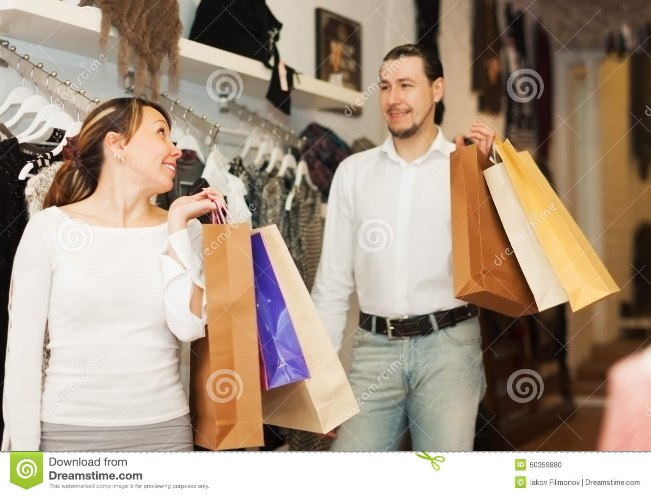 Couple with shopping bags at clothing store together
