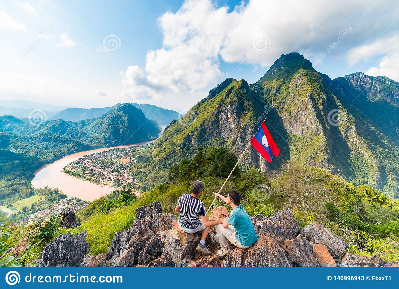 Couple conquering mountain top at Nong Khiaw panoramic view over Nam Ou River valley Laos national flag scenic mountain landscape