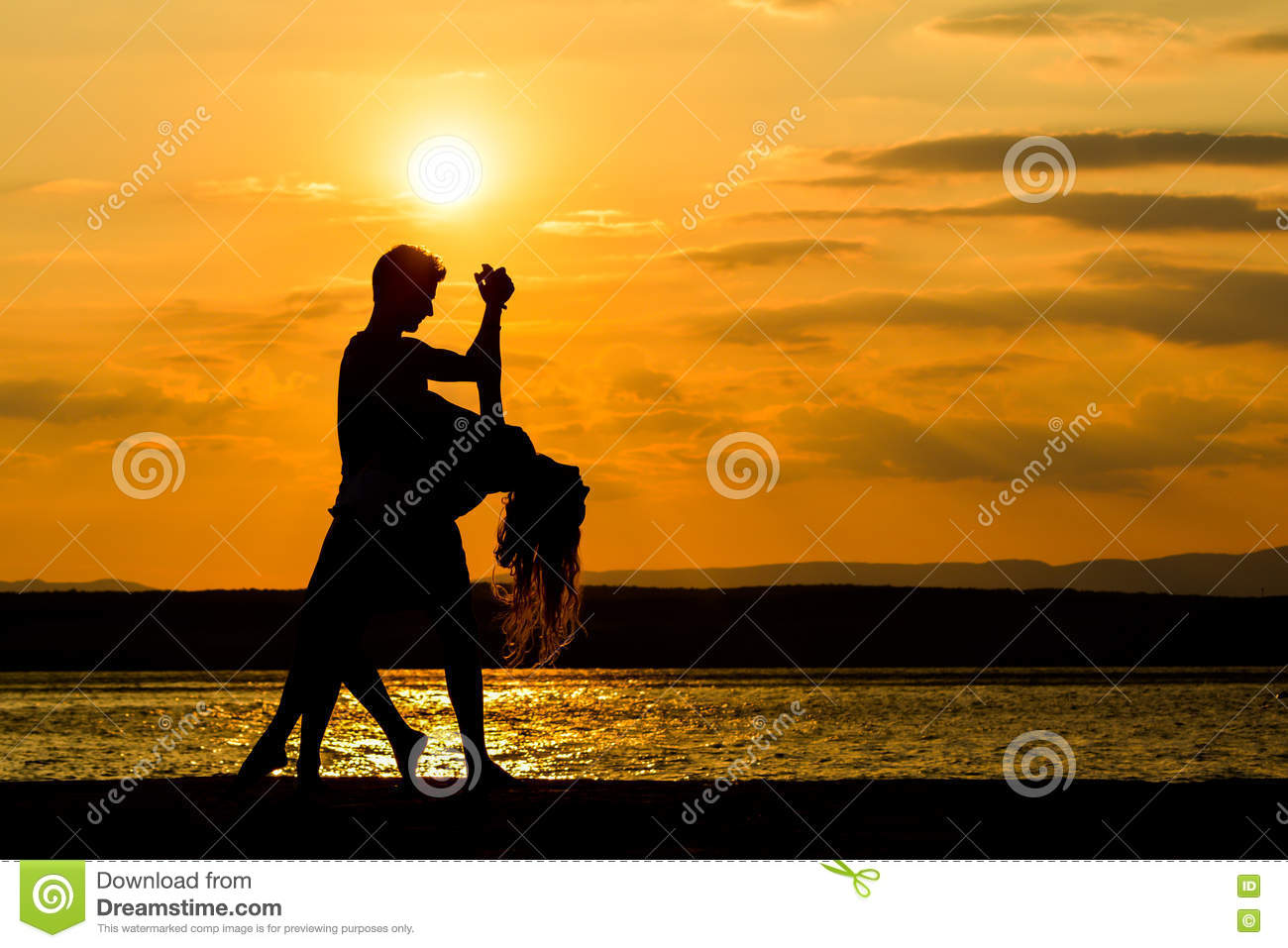 A couple dancing by the sea at sunset