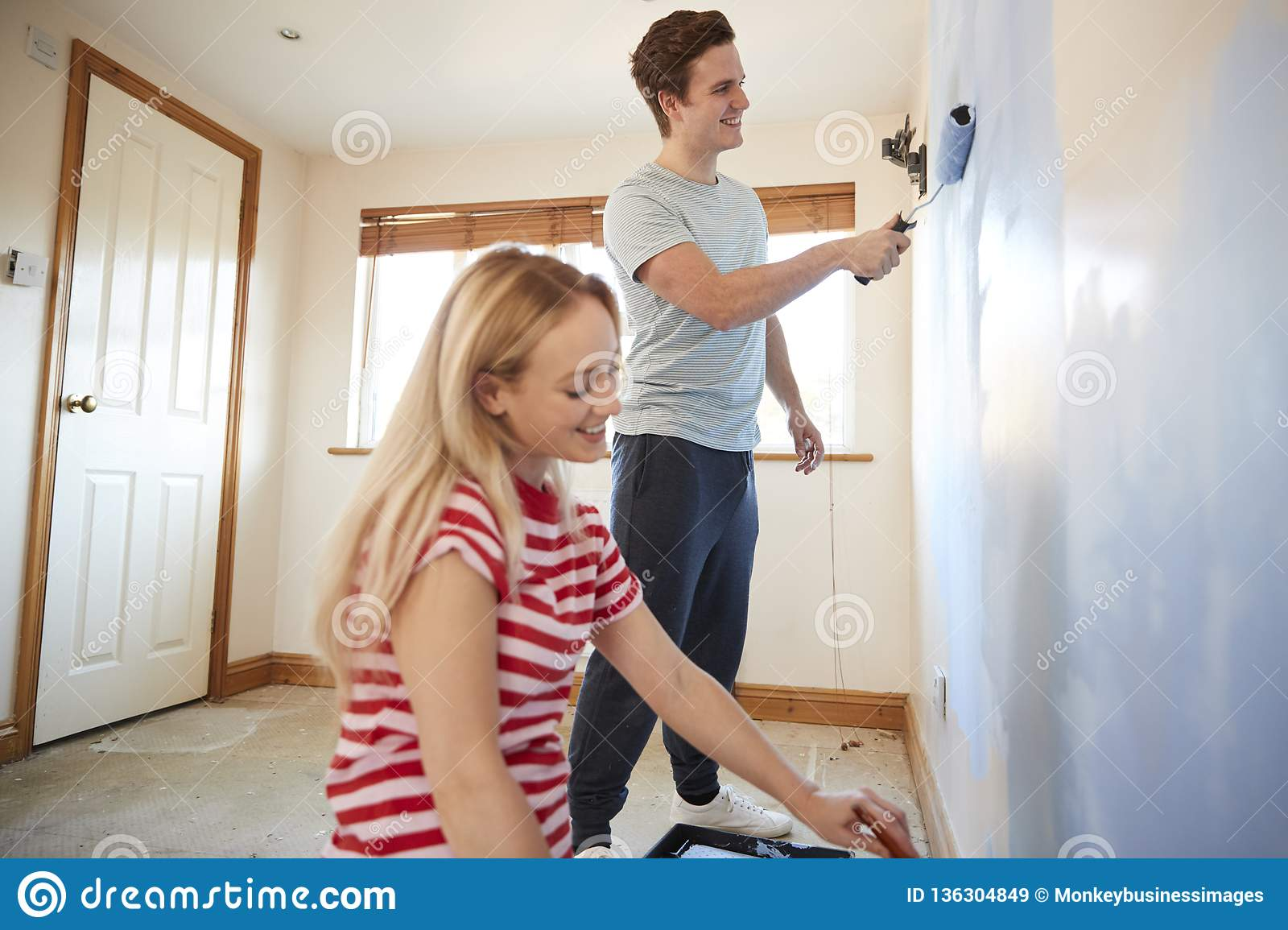 Couple Decorating Room In New Home Painting Wall Together ...