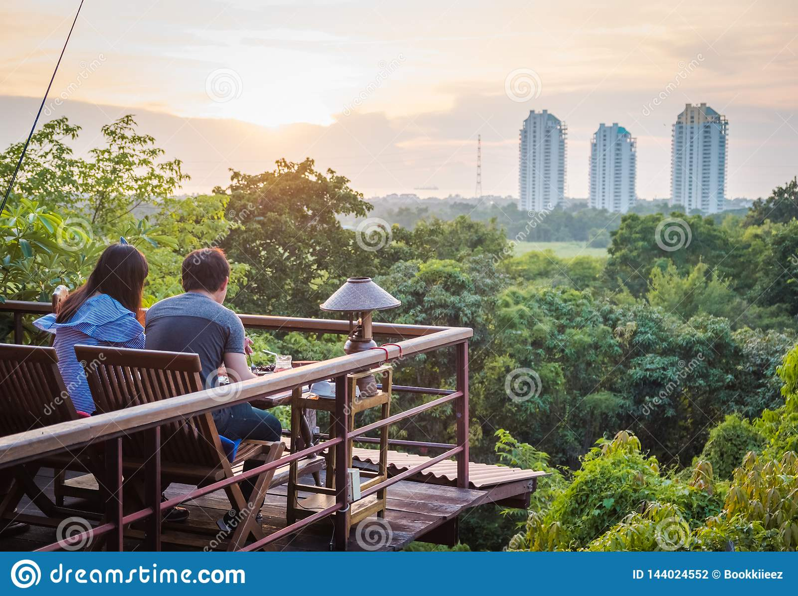 A couple dinning in front of the forest and the buildings.