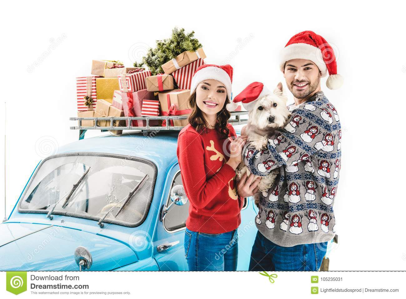 couple with dog and christmas gifts on car