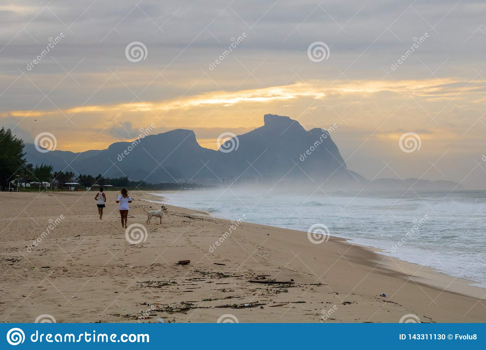 Couple and dog running on the beach of Barra da Tijuca in a beautiful dawn with the stone of Gavea in the background - Rio de Jane