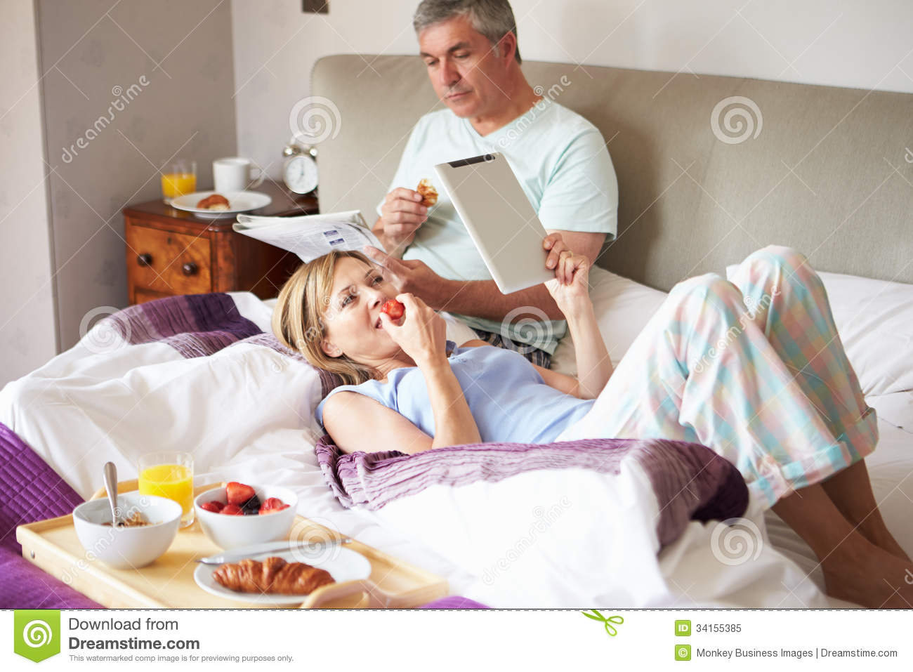 couple eating breakfast in bed with paper and digital. Black Bedroom Furniture Sets. Home Design Ideas