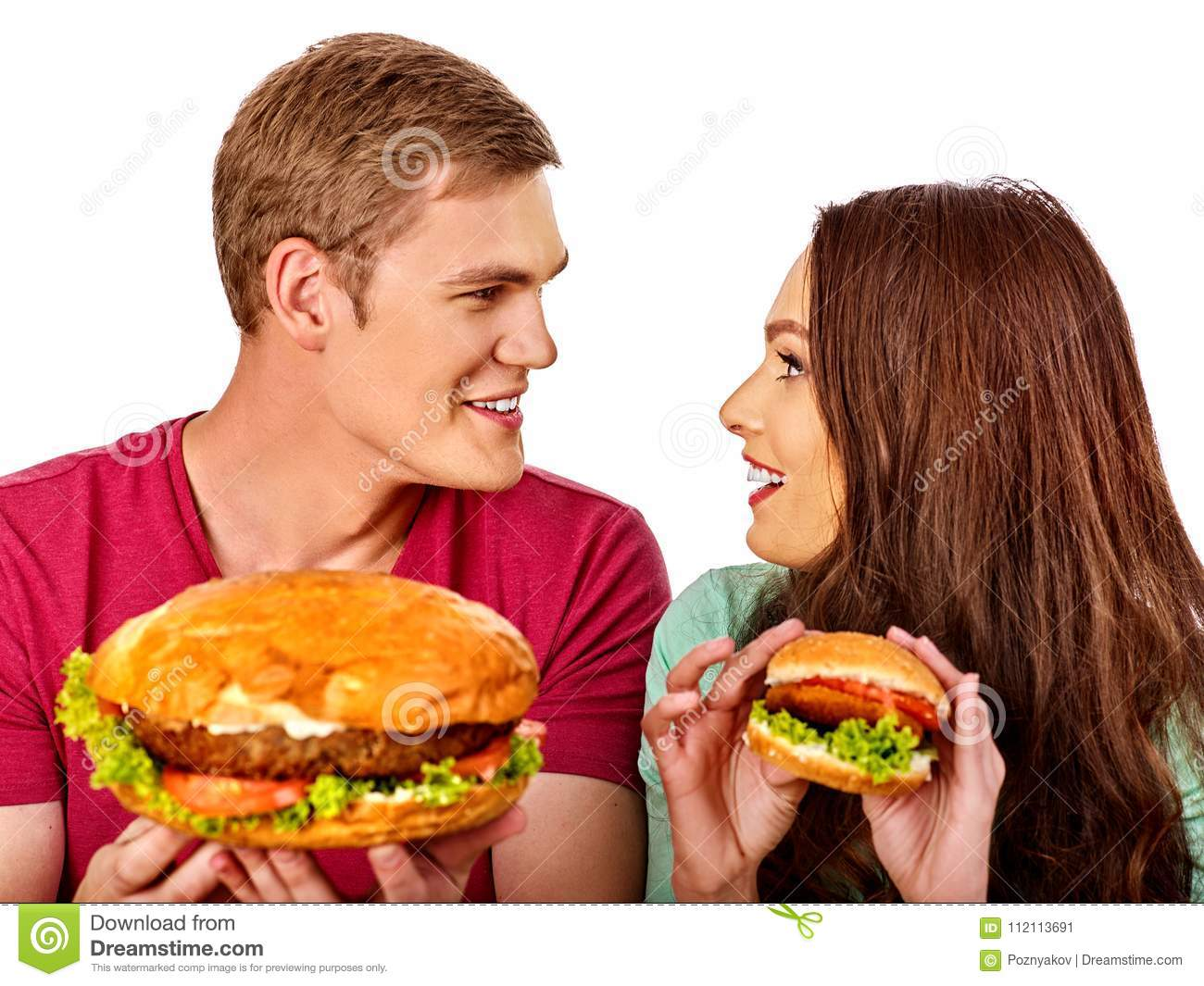 Couple eating fast food. Man and woman eat hamburger with ham.