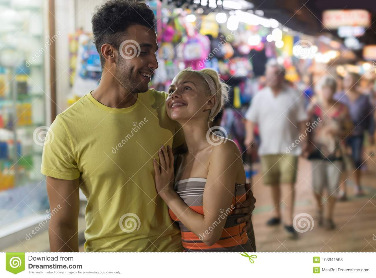 Couple Embracing On Street Market, Mix Race Man And Woman Happy Smiling Looking At Each Other