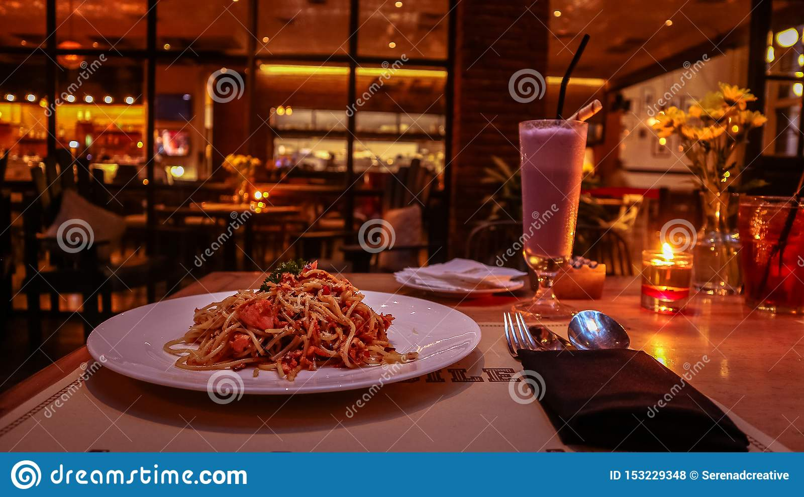 A couple enjoying romantic candle light dinner with aglio olio on the table