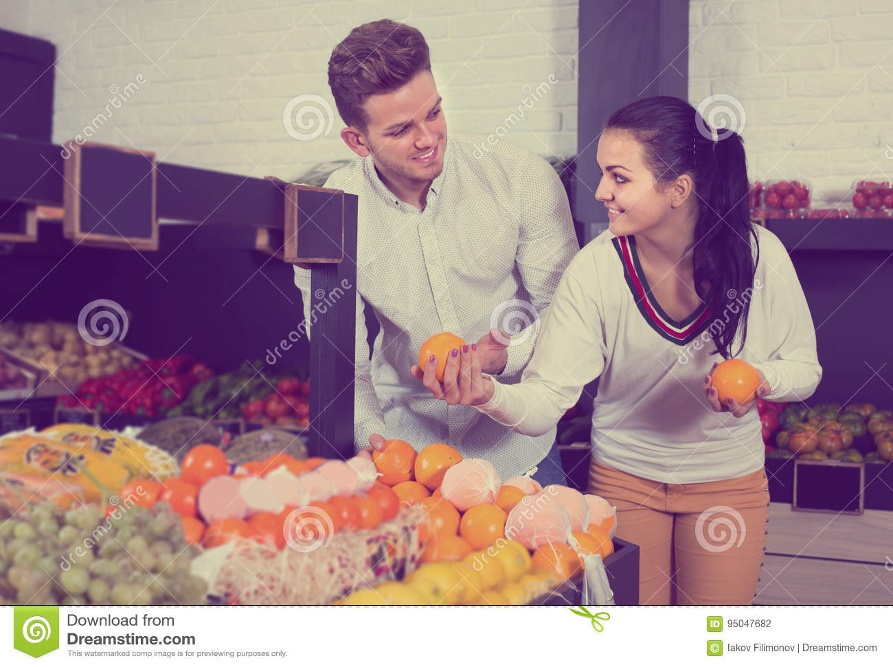 Couple examining various fruits in grocery store