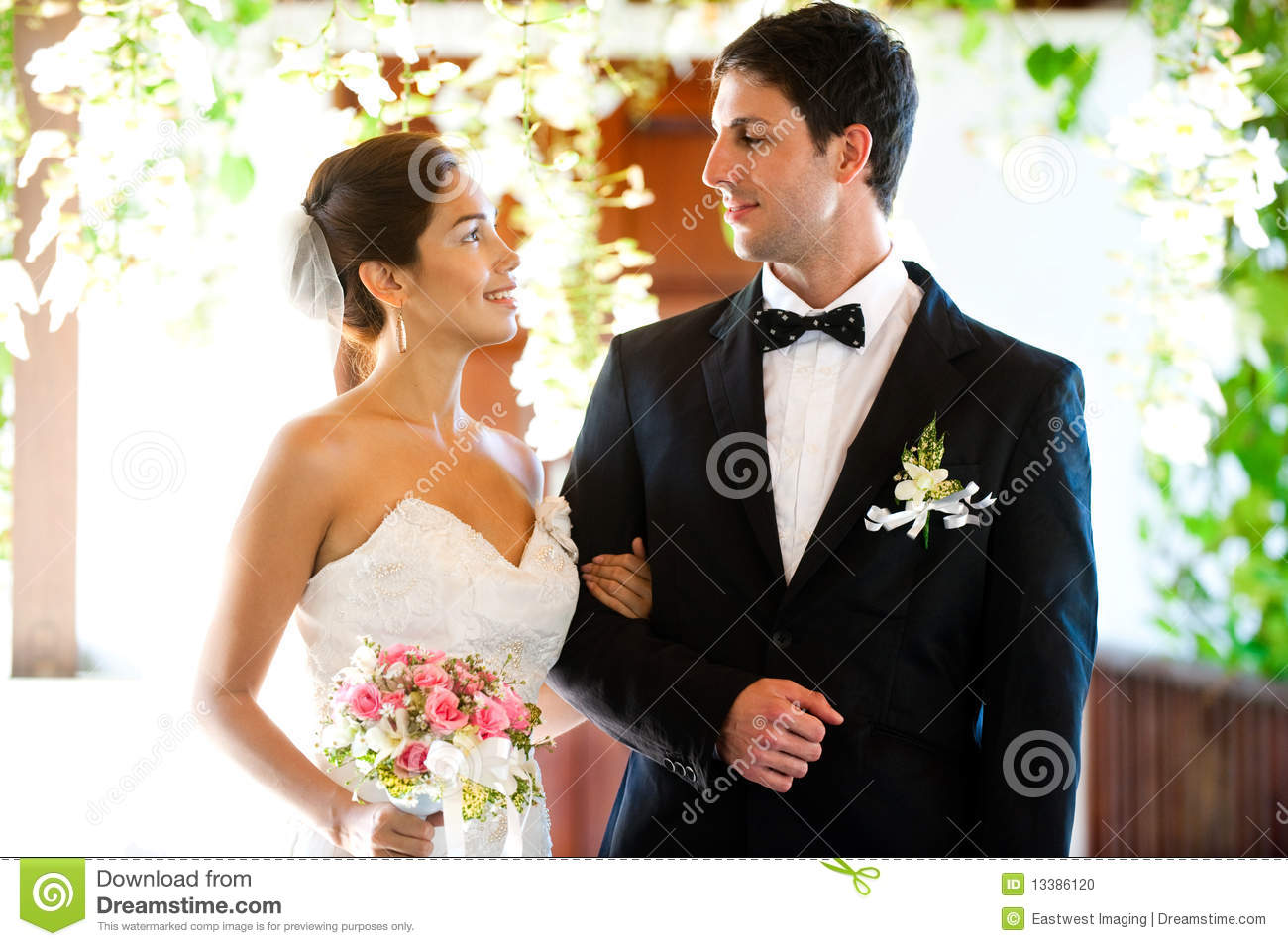 An attractive bride and groom getting married outdoors.