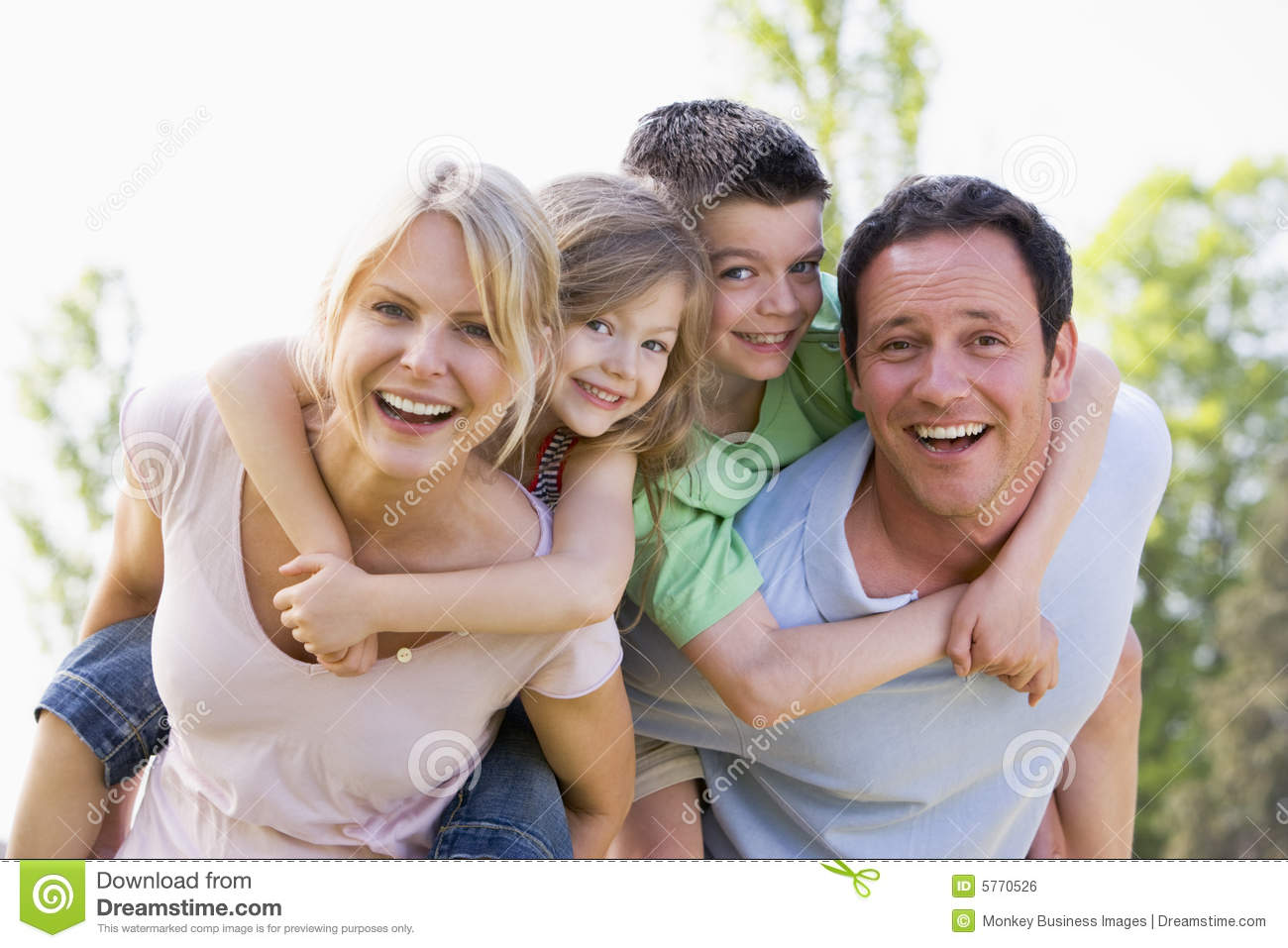 Couple giving two children piggyback rides smiling