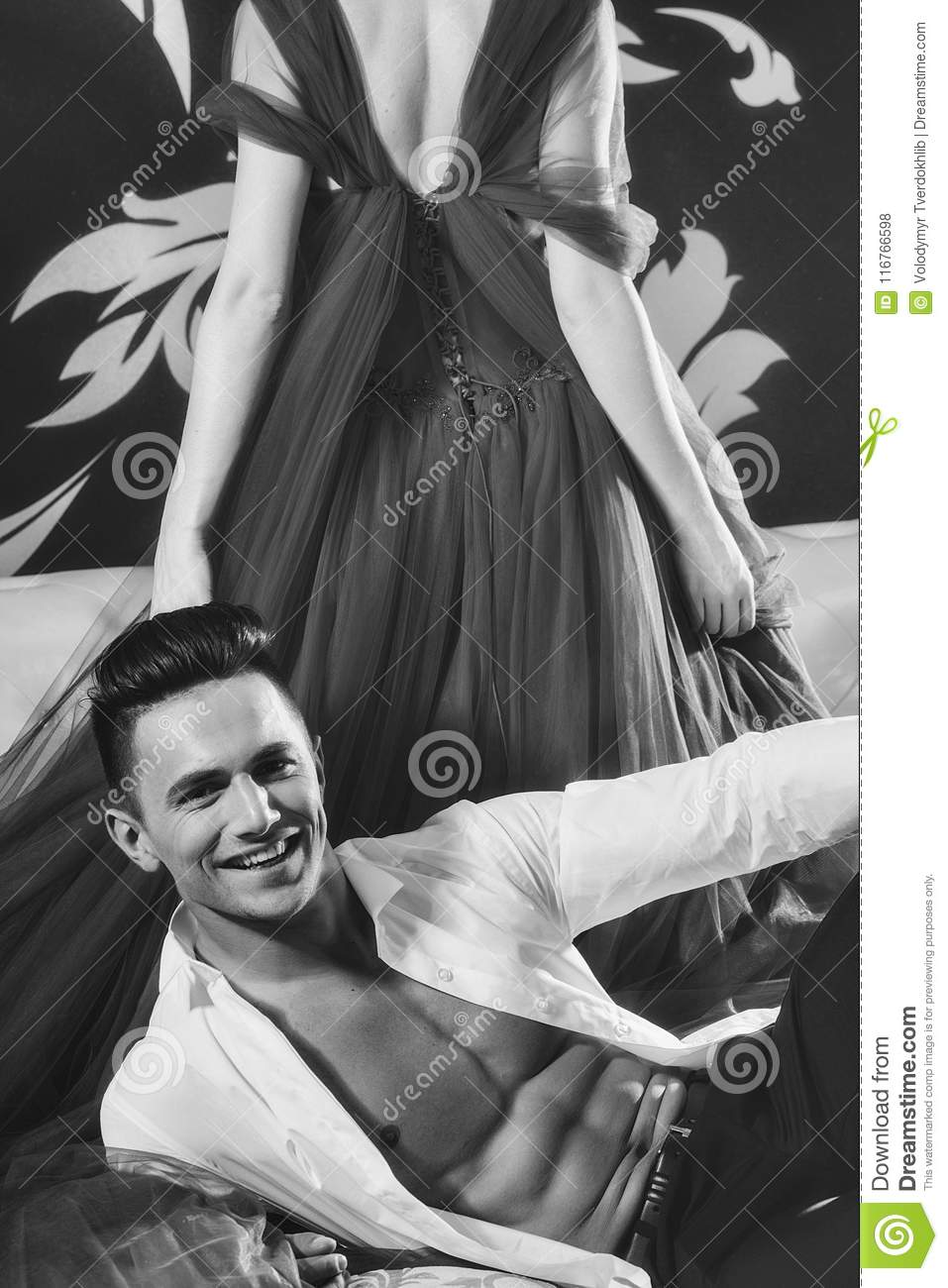 7ab82b70a5585 Couple of handsome man in open shirt with muscular bare torso with pretty  woman in red elegant evening dress with long skirt