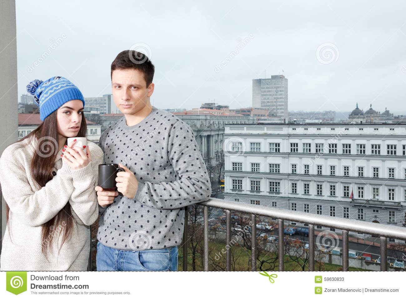 Couple happy in love hugging near railing with cups of tea or co