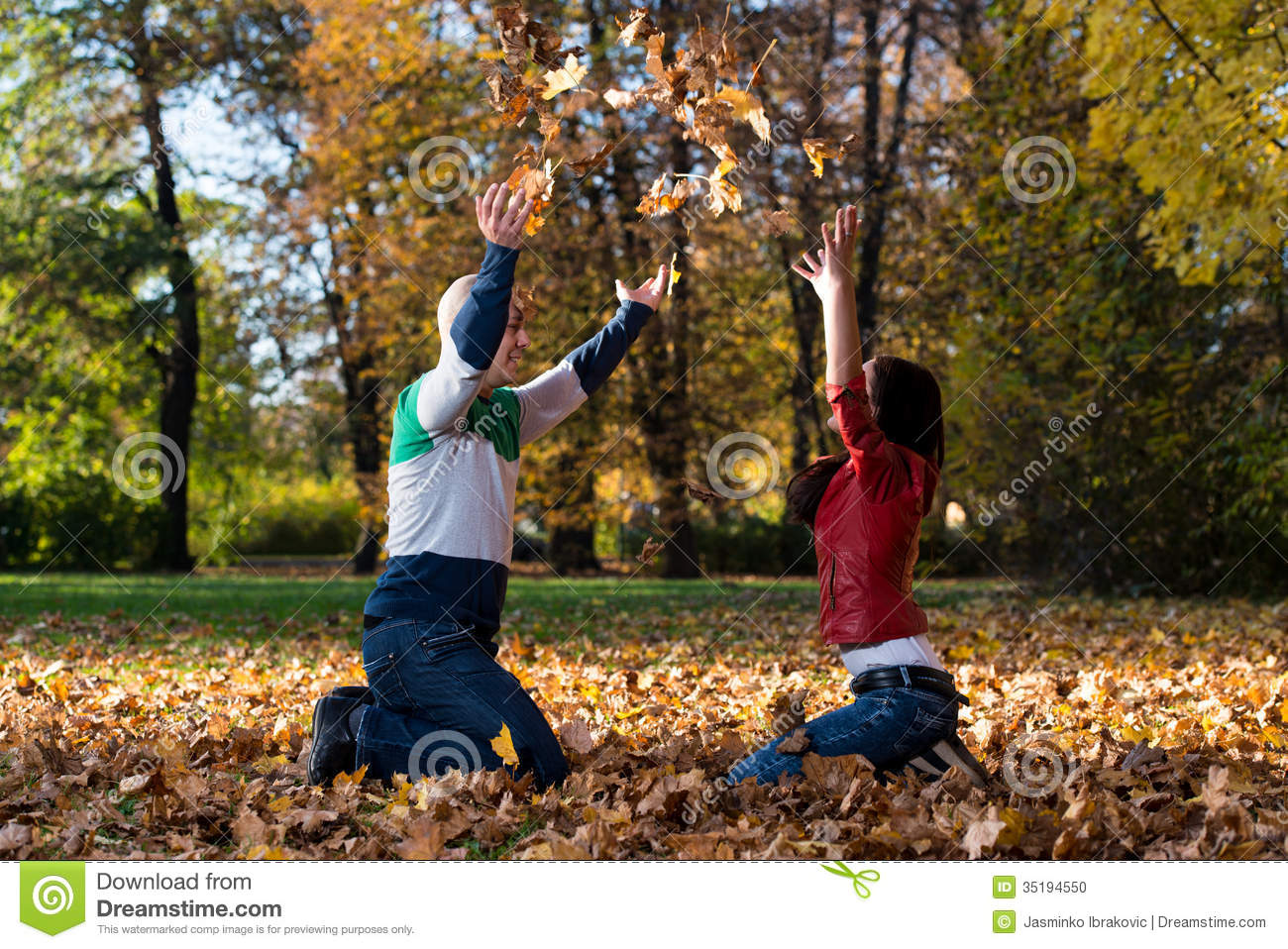 Couple Having Fun With Autumn Leaves In Garden Stock Photo - Image ...