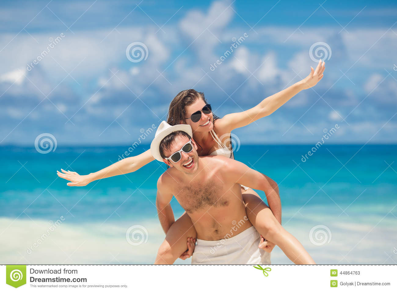 Couple having fun on the beach of a tropical ocean.