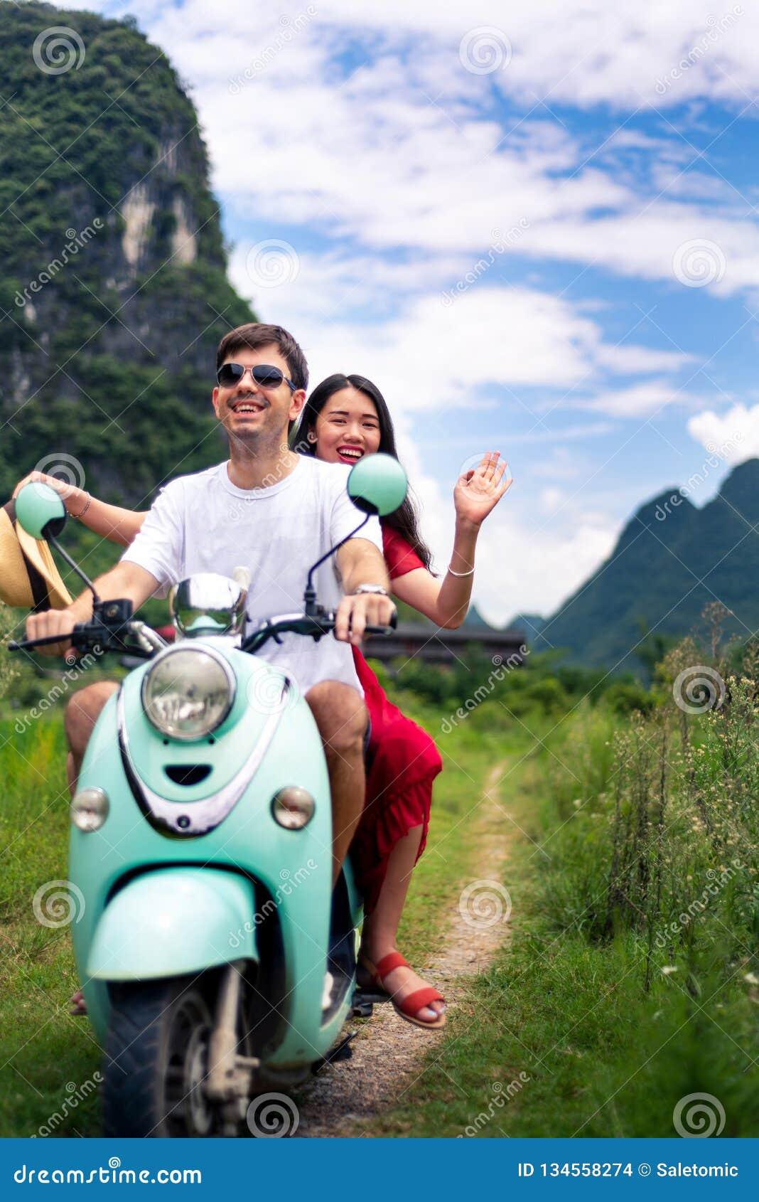 Couple having fun on motorbike around rice fields in China