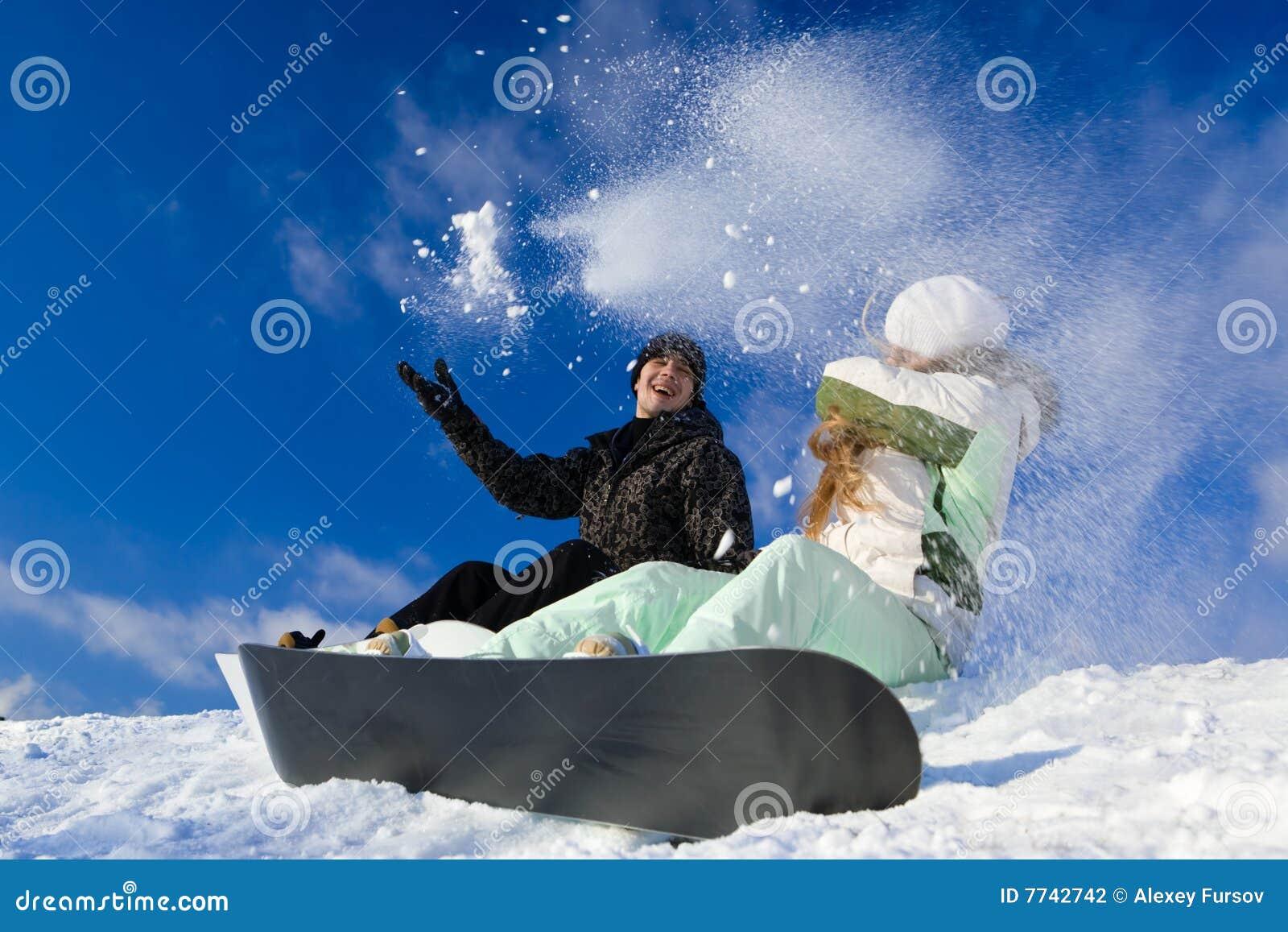 Couple having fun on snowboard