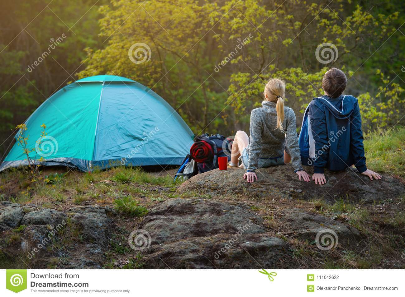 couple of hikers with backpacks resting near the tent in the warm sunshine at sunset. Travel, vacation, holidays and adventure co