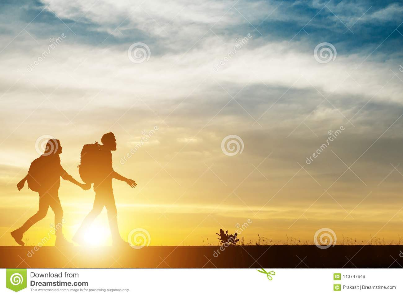 Couple hiking help teamwork and trust silhouette walking during