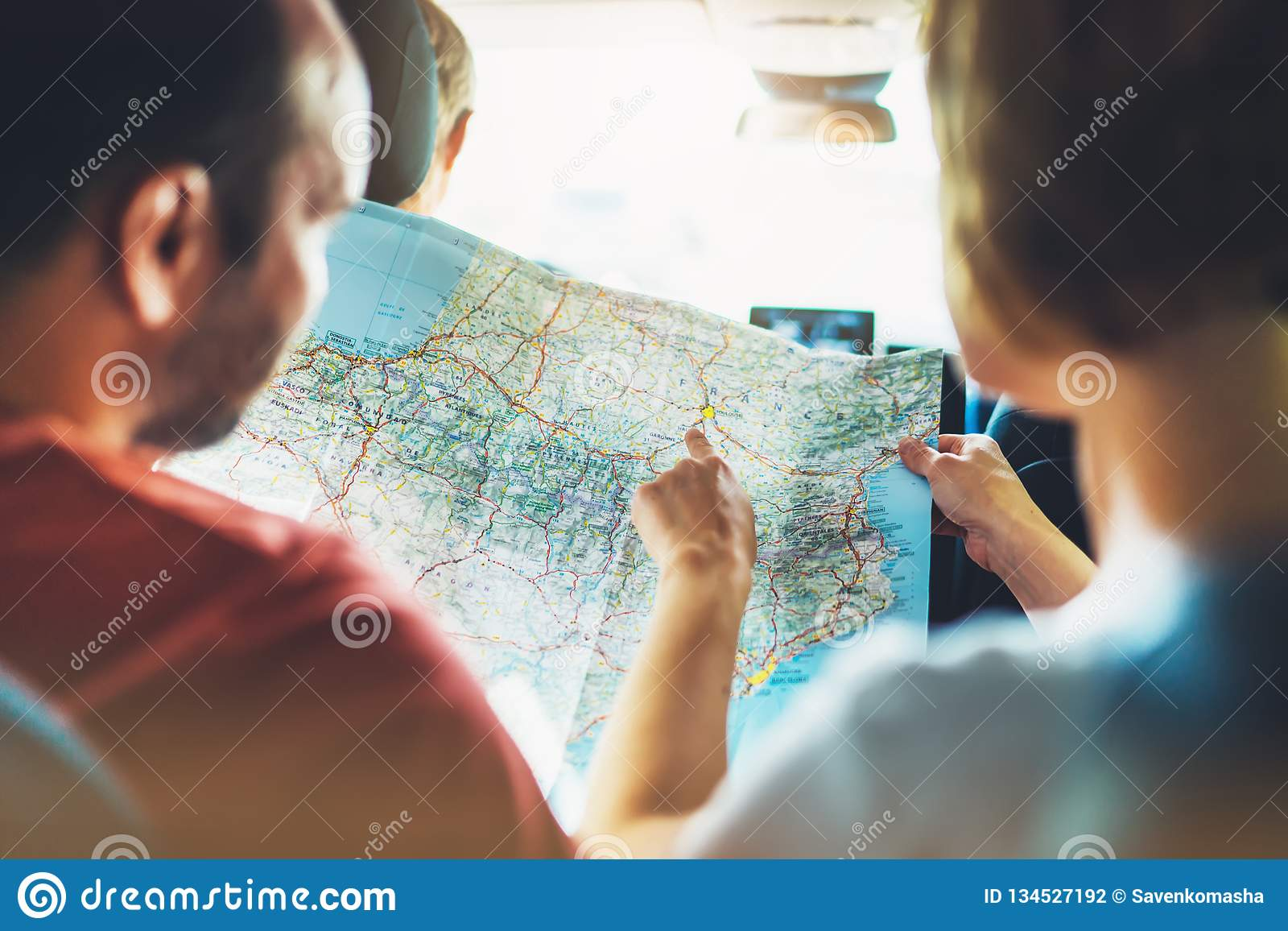 Couple hipster friends looking and point finger on location navigation map in auto car, two tourist traveler together hold in hand