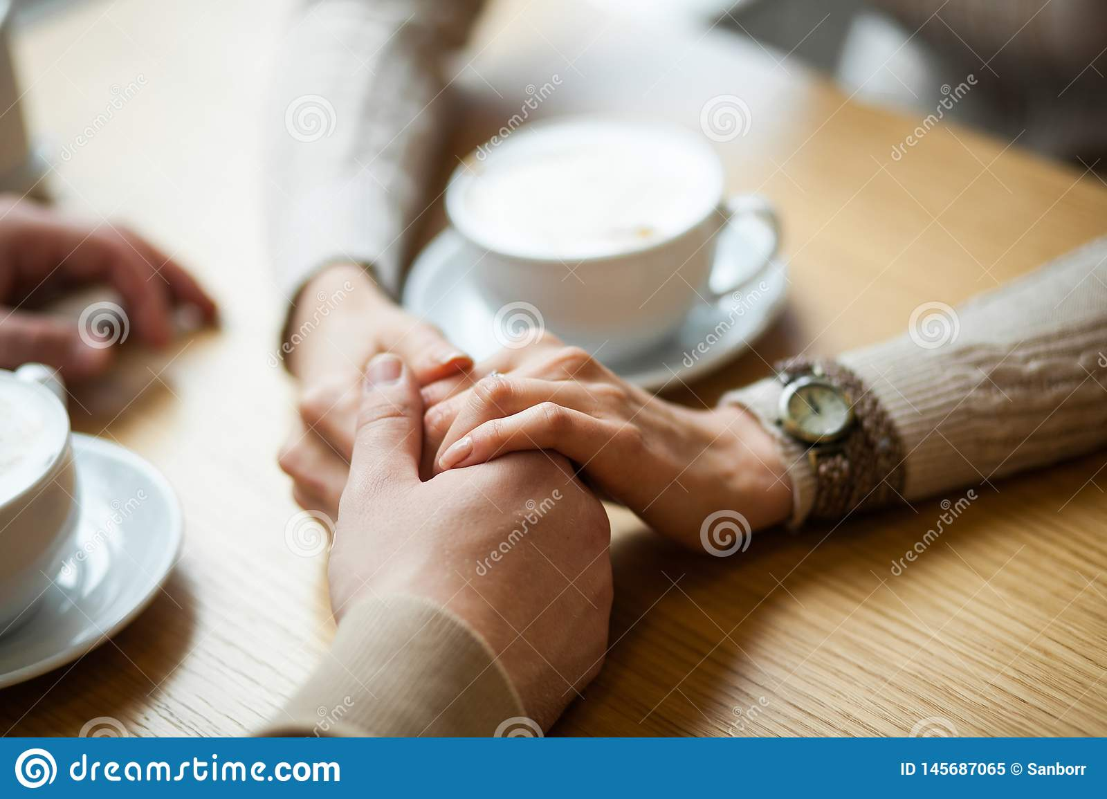 Couple hold hands drinking coffee in cafe, close up of lovers arms on background of wooden table. Breakfast or lunch in restaurant