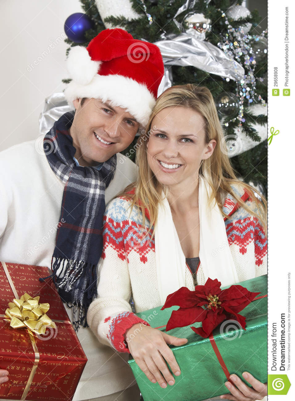 Couple Holding Gifts In Front Of Christmas Tree