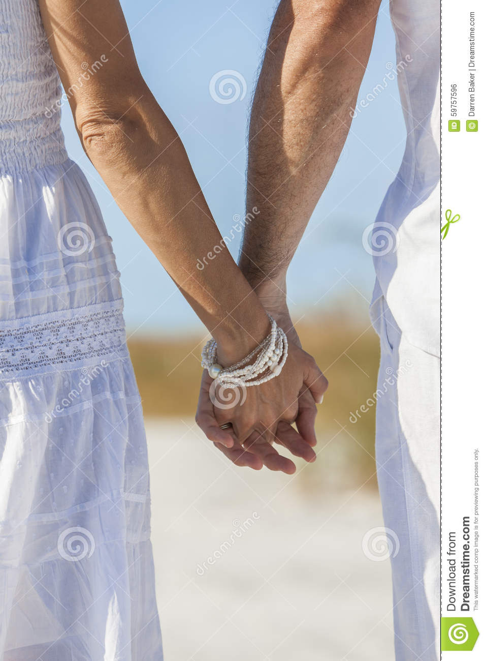 f719dedcc4b6 Rear view of men and women romantic couple in white clothes holding hands  on a deserted tropical beach with bright clear blue sky