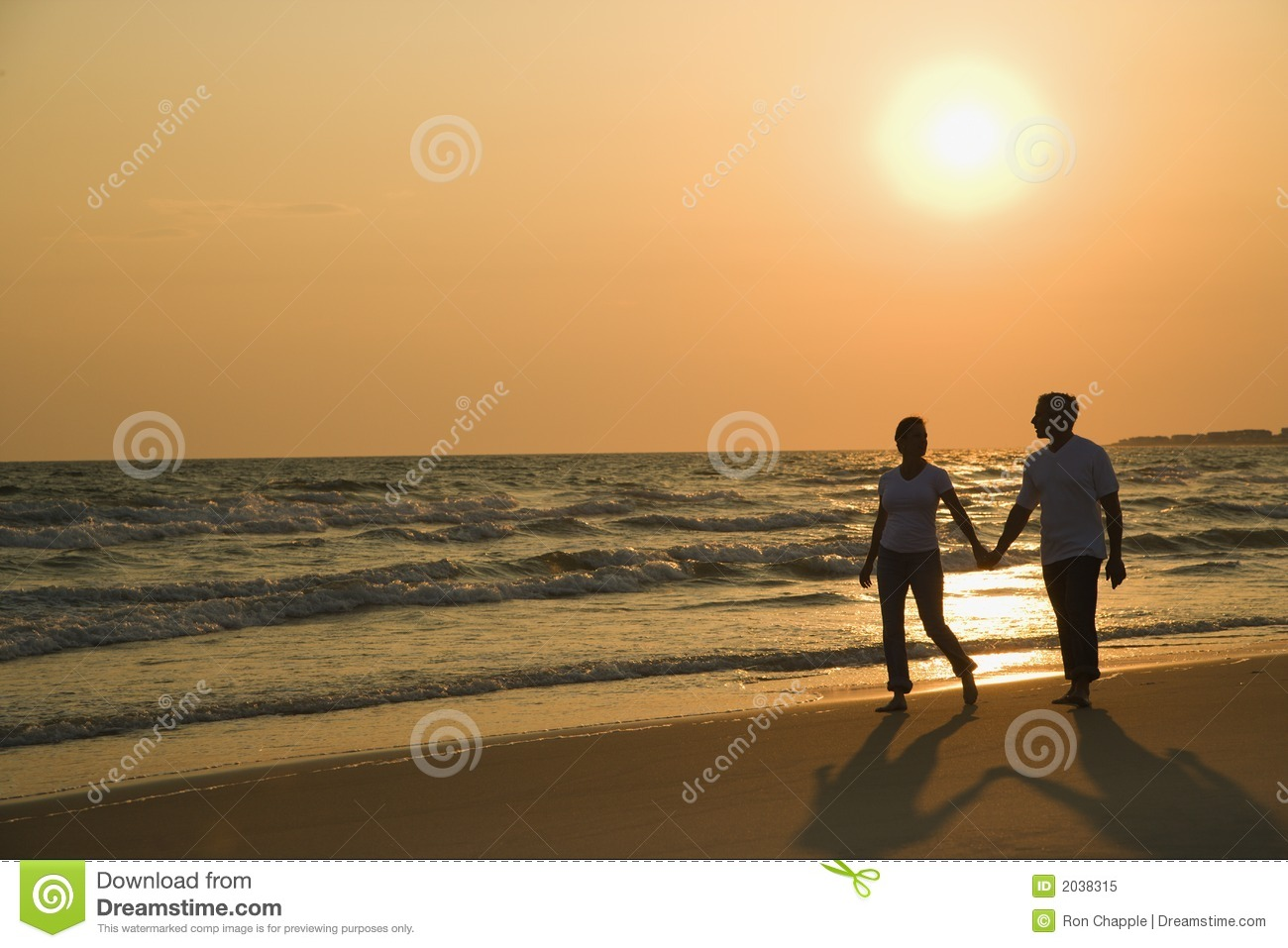 Couple holding hands at sunset.