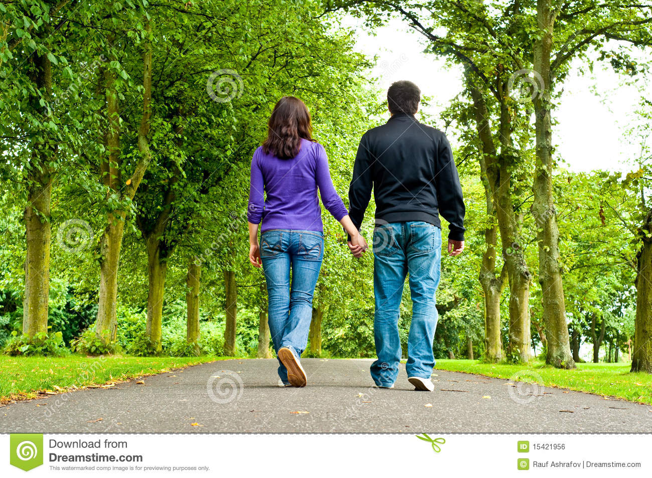 couple holding hands and walking in a park royalty free