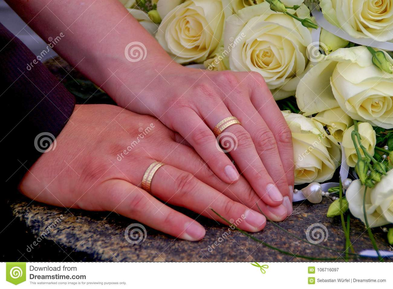 Couple Holding Hands During Wedding With Wedding Rings And Flowers ...
