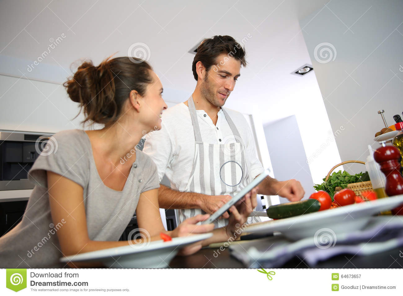 Couple at home cooking dish with tablet stock photo for The web kitchen
