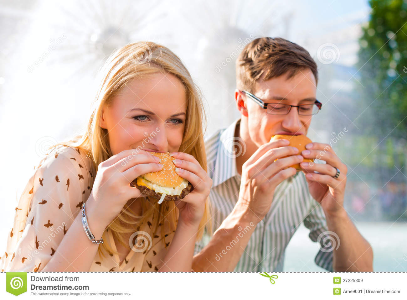 couple is hungry and eating a burger at break royalty free