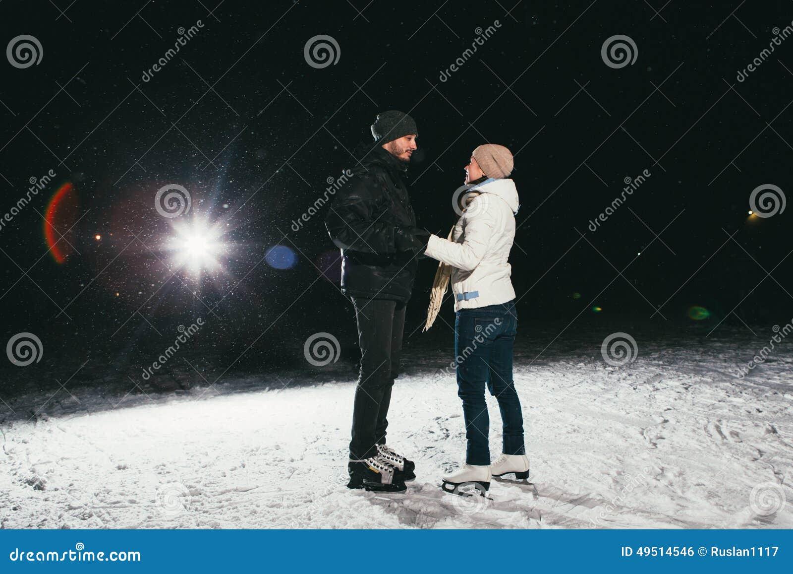 Couple ice skating at night