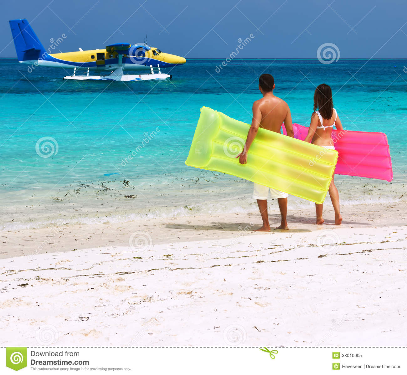 Couple At The Beach Stock Image Image Of Caucasian: Couple With Inflatable Rafts Looking At Seaplane On Beach