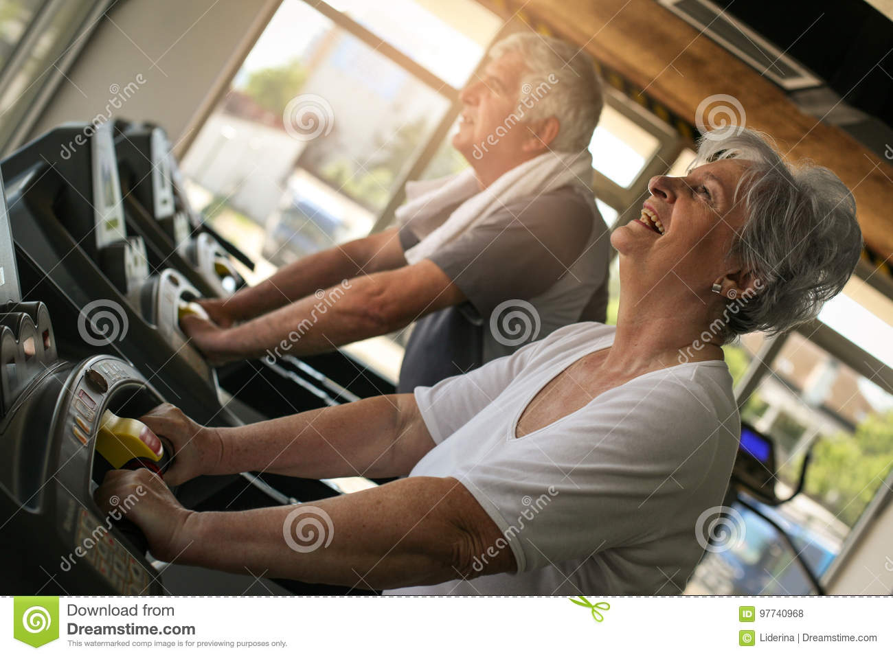 Couple on jogging machine. Senior couple workout in the g