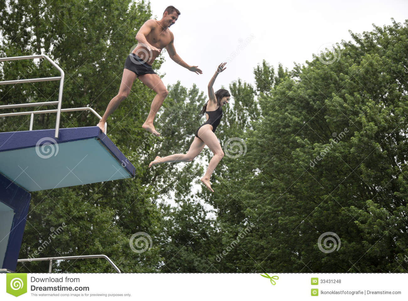 Couple Jumping From A Diving Board Into A Swimming Royalty