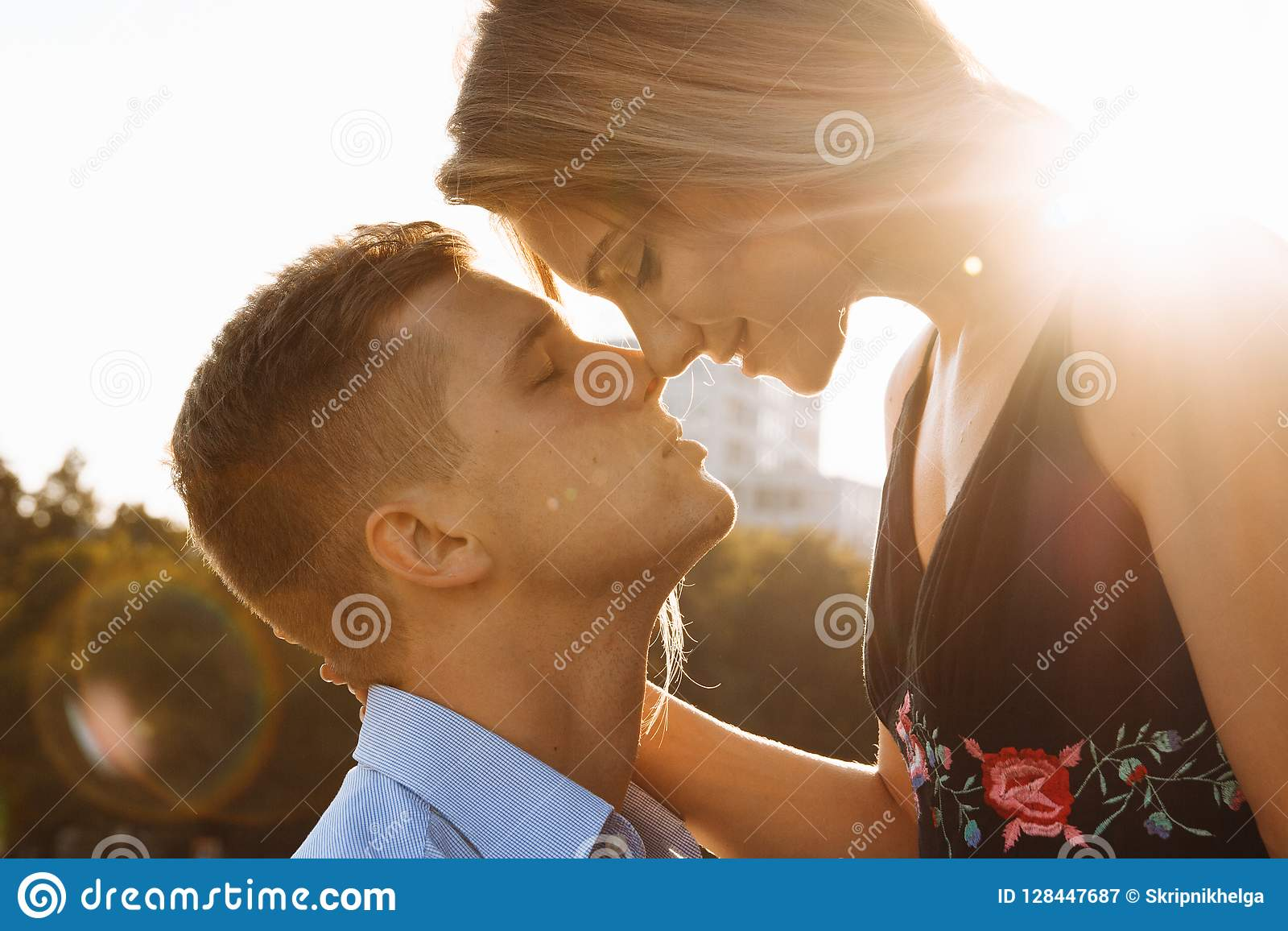 a girl kissing a boy on the neck