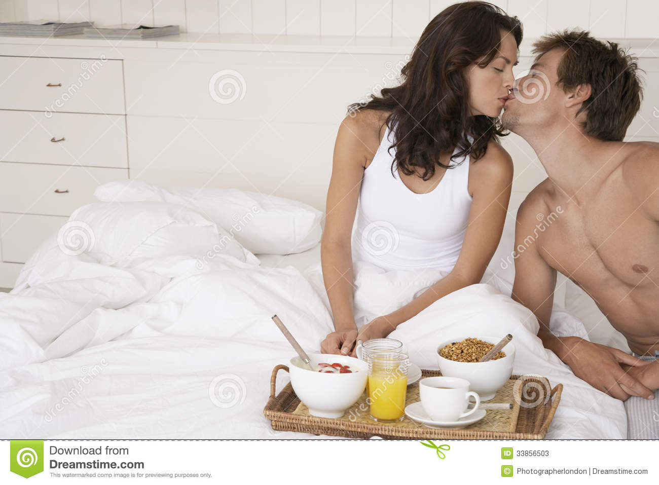 couple kissing by breakfast tray in bed stock photos