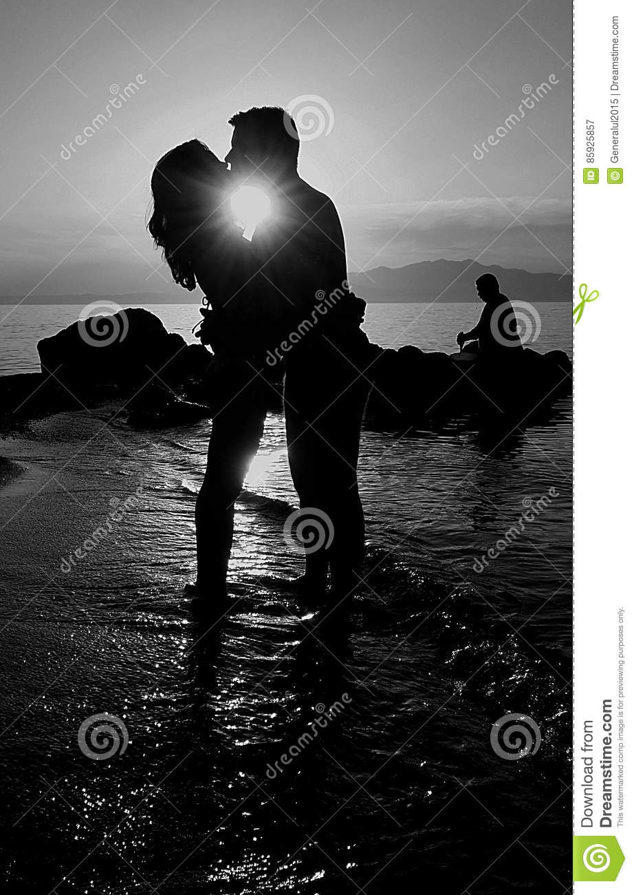 Black and white picture with silhouettes of a couples of lovers kissing picture taken on sea in a summer dramatic sunset sun