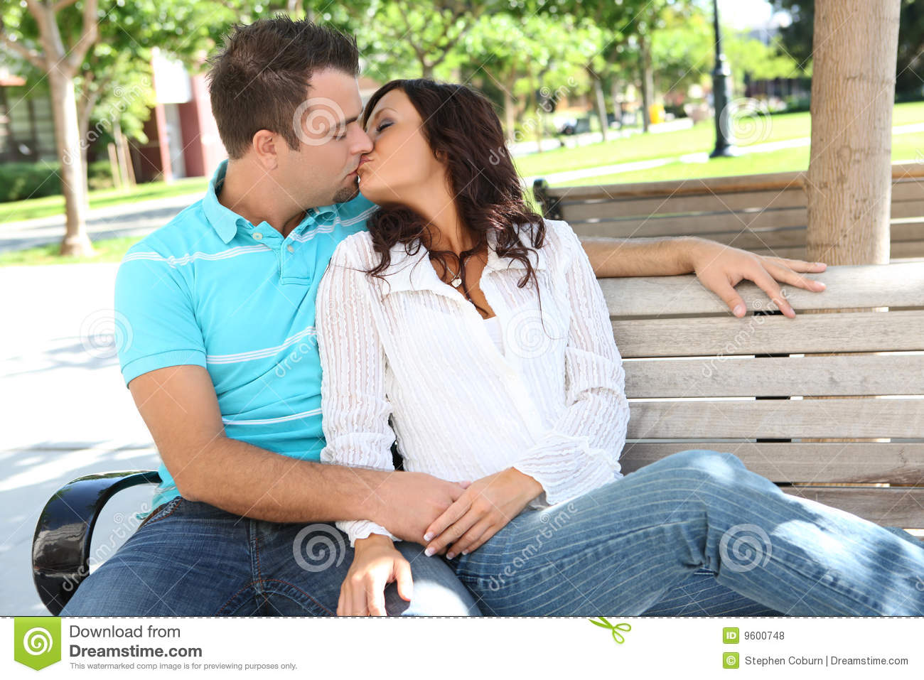 Attractive Couple Kissing On A Bench At College Campus