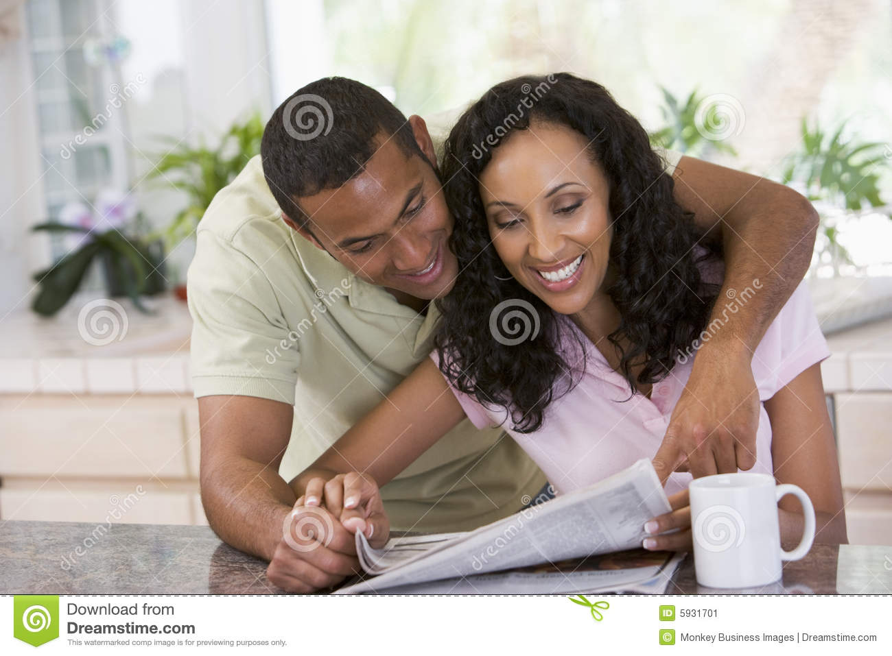Couple in kitchen with newspaper and a coffee