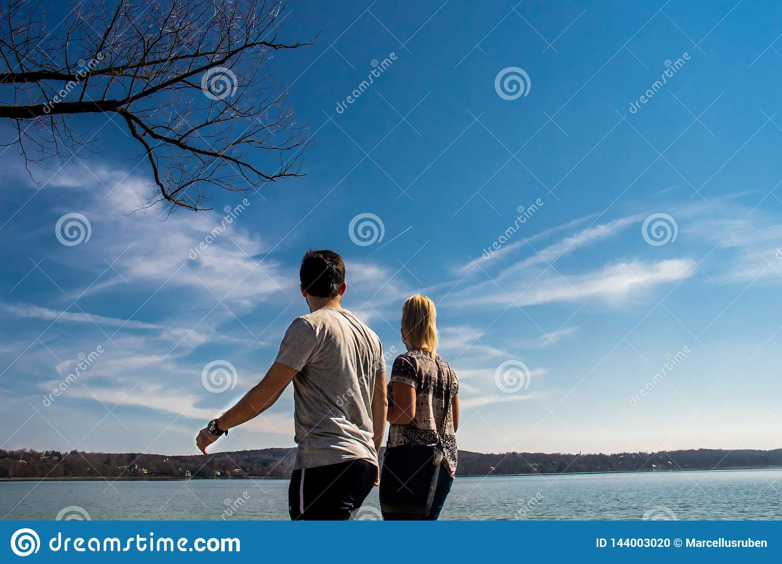 Couple looking at the beautiful lake scenery with clear blue sky background in Starnberg, Germany
