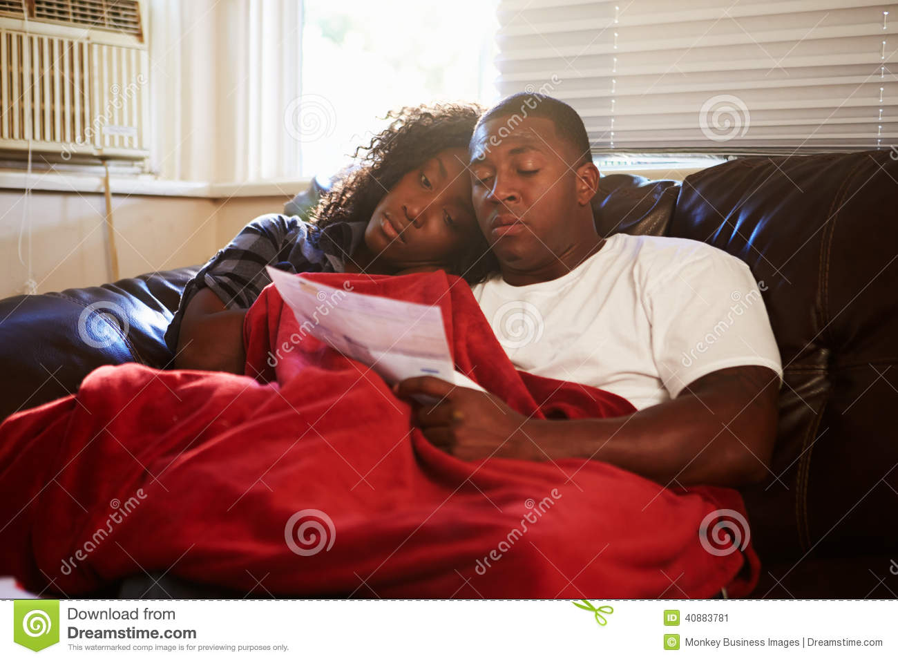 Couple Looking At Bills Keeping Warm Under Blanket At Home