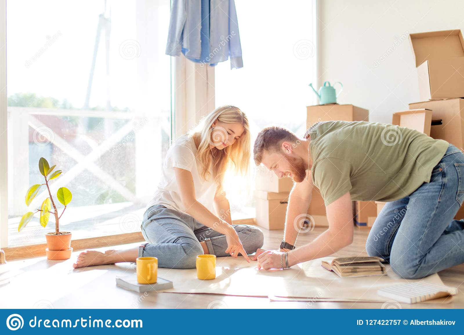 Couple looking blueprints of they new house. Planning interior design