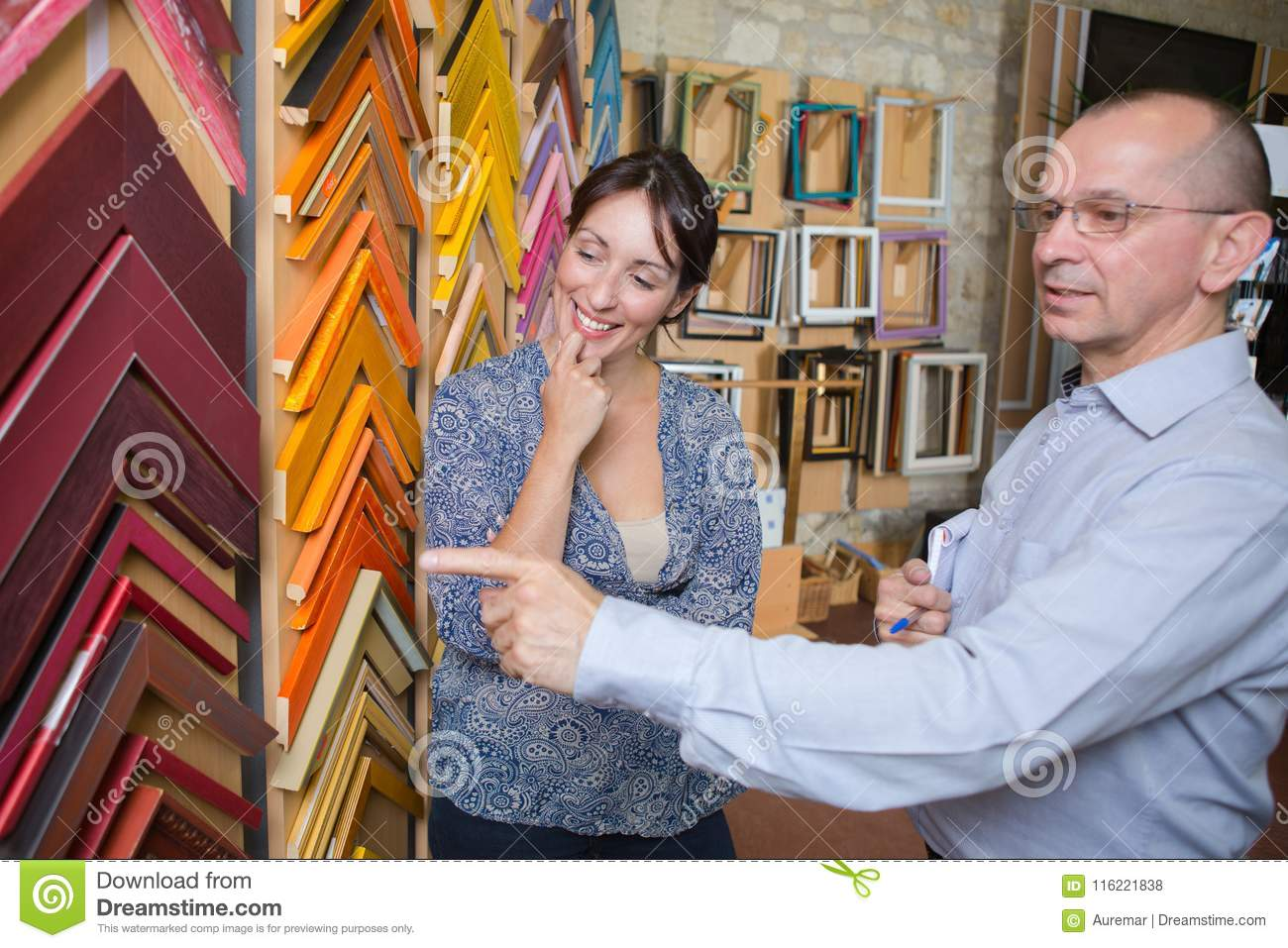 Couple looking at frames stock photo. Image of choosing - 116221838