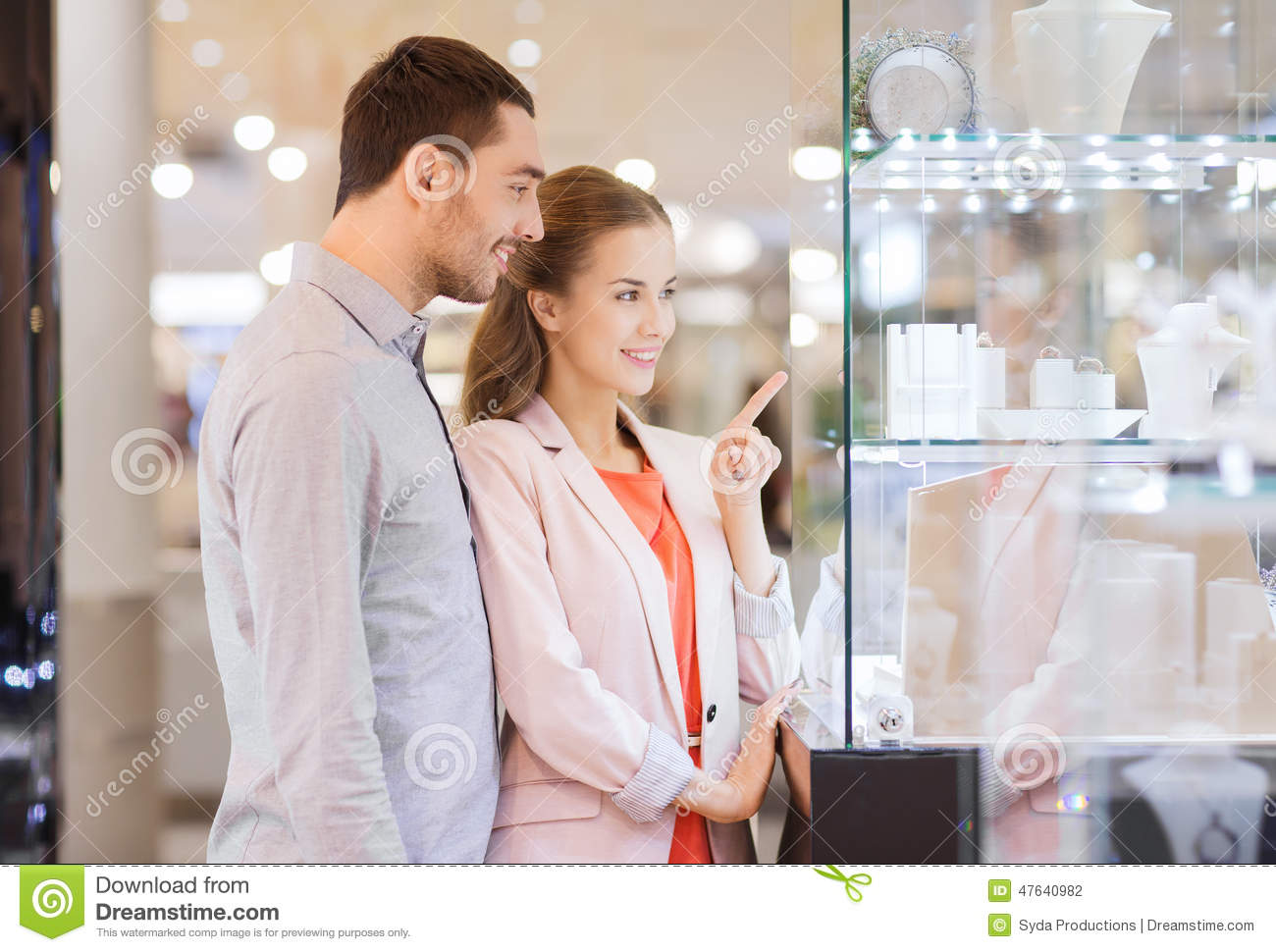 Couple looking to shopping window at jewelry store stock for Jewelry sale online shopping