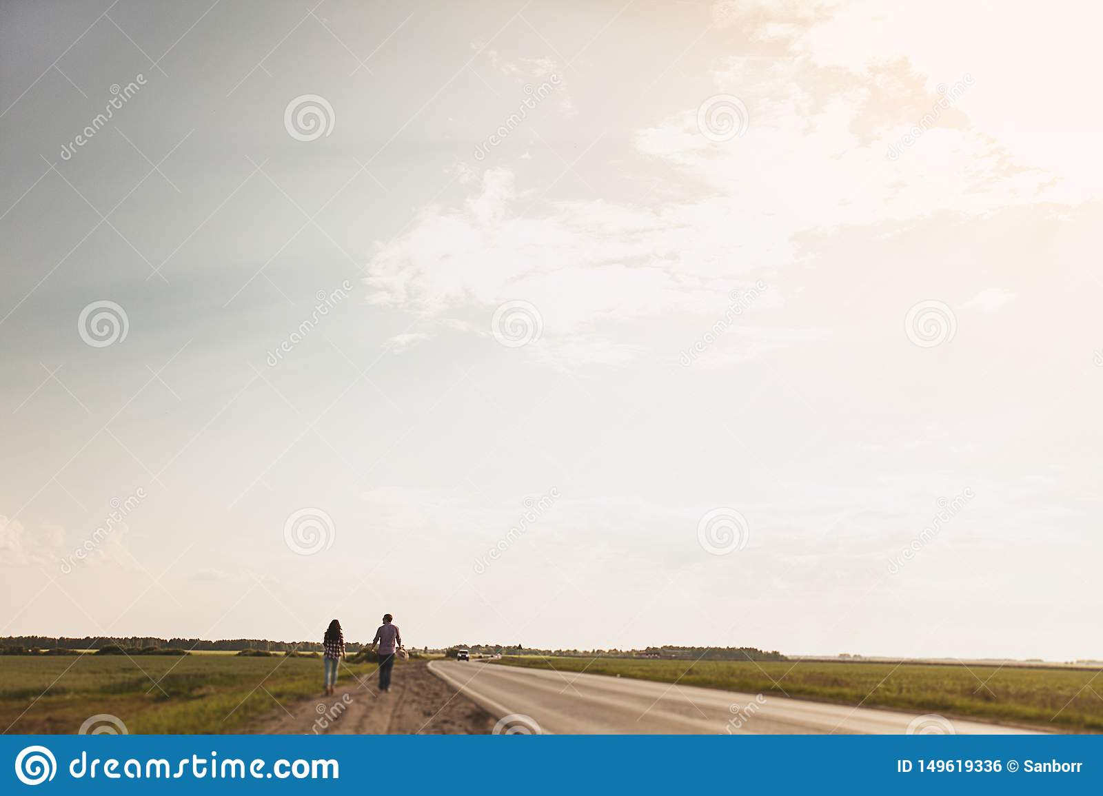 Couple in love is on a country road. The concept of hitchhiking. Rear view. Copy space for text
